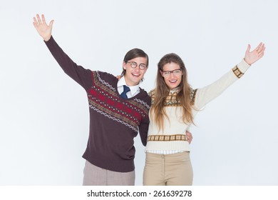 Happy geeky hipster couple embracing on white background