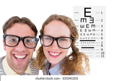 Happy geeky hipster smiling at camera against eye test