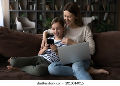 Happy gen Z girl and mom relaxing on couch with gadgets. Mother and little daughter kid using parental control app on smartphone, playing online game, watching video on laptop, browsing internet