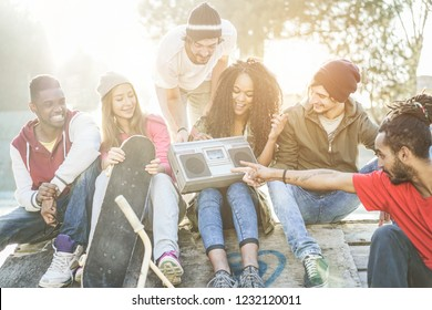 Happy generation z friends listening music and laughing in city park - Young diverse culture people having fun together - Youth, millennial lifestyle, multiracial concept - Focus on left guys faces