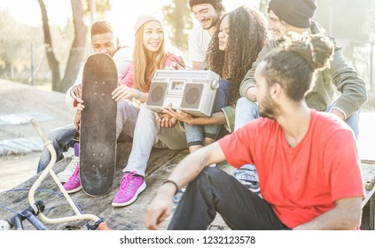 Happy generation z friends listening music and laughing in city park - Young diverse culture people having fun together - Youth, millennial lifestyle, multiracial concept - Focus on african girl face