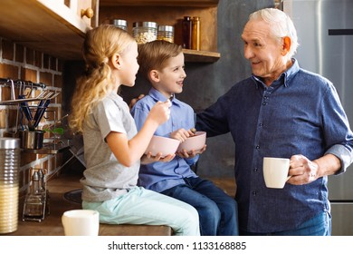 Happy generations. Joyful smiling elderly man drinking tea while enjoying time with his grandchildren
