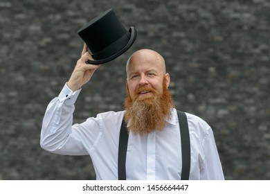 Happy genial man politely doffing his top hat in greeting as he gives the camera a beaming friendly smile over grey