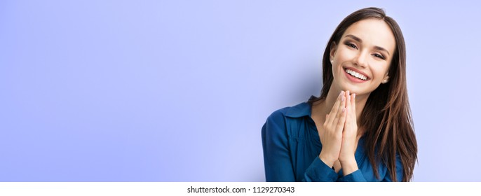 Happy gesturing smiling young woman in casual smart blue clothing, over violet background, with copyspace for slogan, advertising or text message. Banner composition.