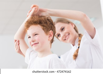 Happy ginger boy exercising with professional therapist