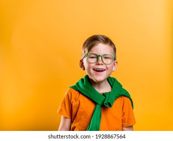Happy ginger boy with freckles on Saint Patrick Day. Kid in green glasses and orange t-shirt. Patrick party with Irish culture and traditions. Bright child boy with leprechaun for a St. Patrick's Day