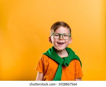 Fröhlicher Ingwer mit Sommersprossen am St. Patrick Day. Kind in grüner Brille und orangefarbenem T-Shirt. Patrick Party mit irischer Kultur und Traditionen. Heller Junge mit Kobold zum St. Patrick's Day