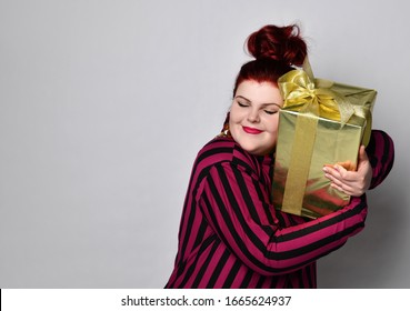 Happy ginger woman in black and purple striped dress, crown and earrings. Holding golden gift box tied with ribbon and bow, looking joyful, posing isolated on white. Close up, copy space