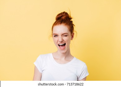 Happy ginger woman in t-shirt winks at the camera over yellow background