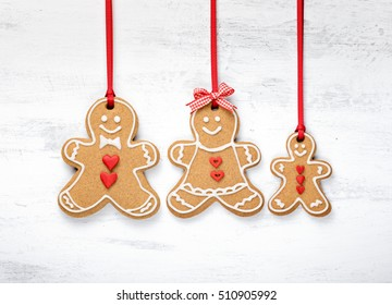 Happy Gingerbread man cookie family hanging on white background.