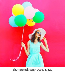Happy girl with an air colorful balloons is having fun in summer on a pink background