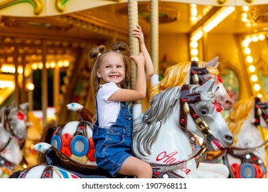happy girl in an amusement park rides a horse on a carousel in the summer