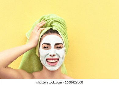 Happy girl applying facial mask - Young woman having skin care spa day - Beauty clean treatment day and cosmetology products concept