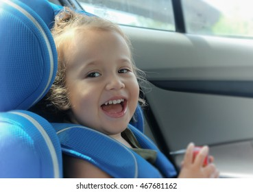 Happy girl in an automobile blue car seat. MIxed Asian-Caucasian little girl. Two years six months old toddler. Curly blonde hair. Big smile. Happy face.