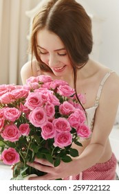 happy girl with big bouquet of pink roses, received as a gift