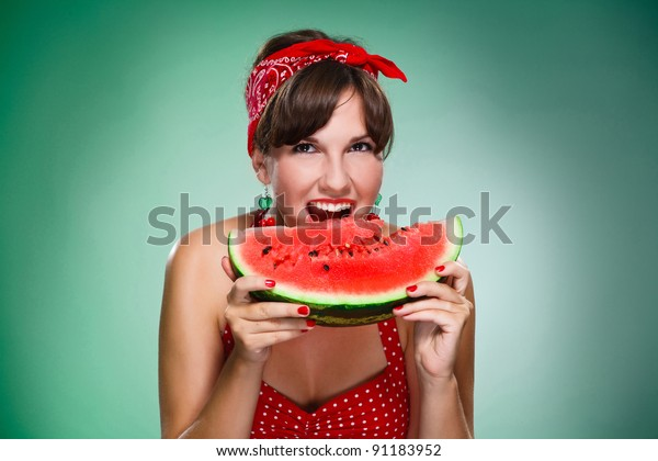 happy girl bitten by a watermelon, isolated green background.