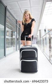 Happy girl in black overalls and with a suitcase leaves on a journey. Waiting for her flight at the airport. Focus on the suitcase