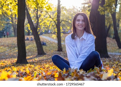 Happy girl in blue jeans and white shirt sits on fallen yellow leaves. Beautiful young woman is sitting on the ground in autumn park. Contre-jour, glares. Evening sunlight.