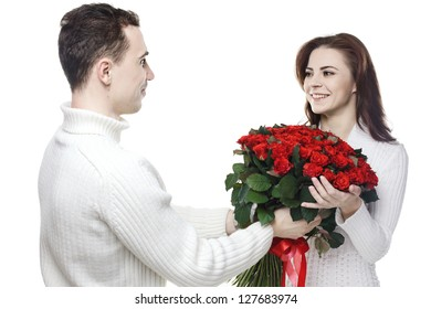 happy girl with bouquet of red roses kissing her boyfriend