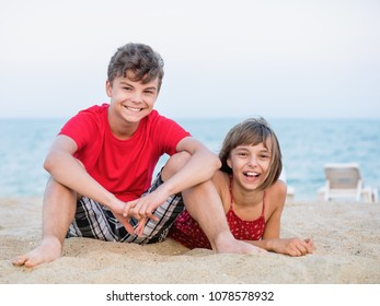Happy girl and boy playing on sea shore at sandy beach during summer holiday. Cute children - brother and sister on vacation, outdoors.