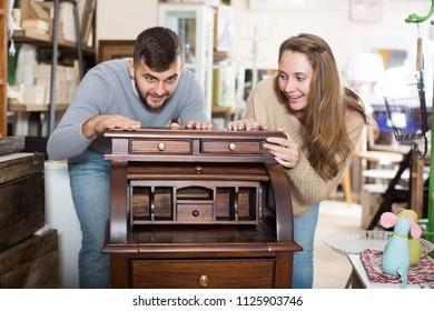 Happy girl with boyfriend choosing vintage cabinet in furnishings store