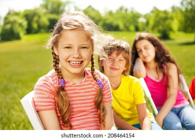 Happy girl with braids and her friends sitting