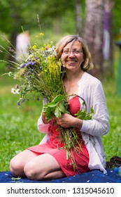 happy girl with bunch of wild flowers in the park