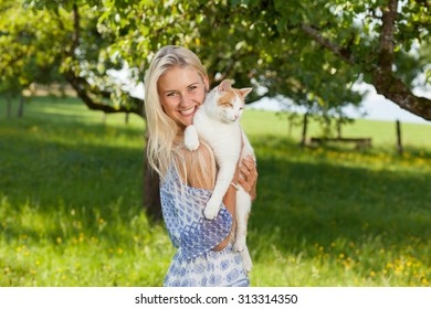 Happy girl with a cat on a summer flower meadow outdoor
