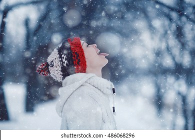 happy girl catches snowflakes mouth