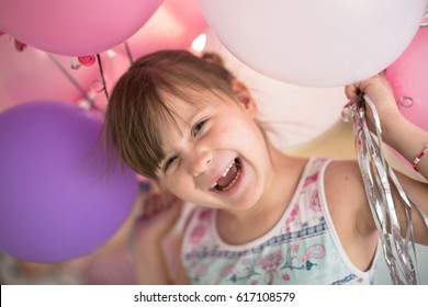 Happy girl child without one tooth with balloons, on a light background, the concept of a happy childhood, home lifestyle