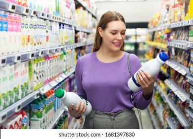 Happy girl choosing milk bottle in market