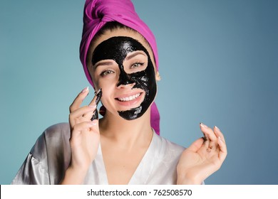 happy girl cleanses the pores on her face with a black mask
