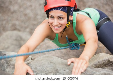 Happy girl climbing rock face wearing red helmet