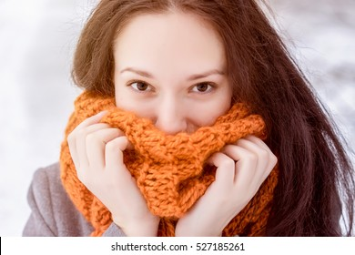 Happy girl Close up portrait. Beautiful lady wearing warm cloth in winter. Brunette woman in the orange scarf smiling. Snowing beauty fashion concept