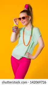 Happy girl with colorful clothes, yellow background