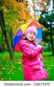 happy girl with  a colorful umbrella in he autumn park