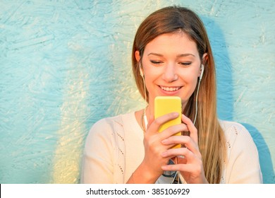 Happy girl connected to social media network and having fun with smartphone. Young woman smiling and typing on the phone against blue wooden background. Lifestyle concept of new trends and technology.