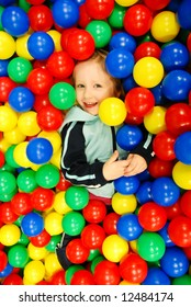 happy girl covered by a pile of colorful balls