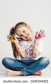 Happy girl covered in paint sitting on the floor. Creativity. Childhood artist.