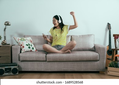 happy girl dancing in comfort house sitting on couch indoors. cheerful asian chinese woman in headphones holding cellphone relax on sofa in apartment in summer holidays. joyful lady enjoy free time