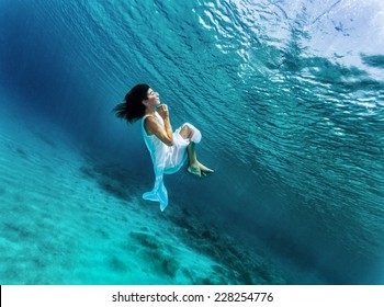 Happy girl dancing underwater, wearing stylish dress, luxury sea performance, active summer vacation, sport and art concept