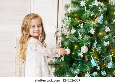 happy girl decorates the Christmas tree