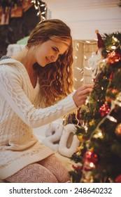 Happy girl decorates a ?hristmas tree