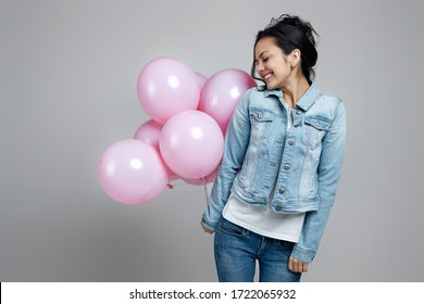 happy girl in denim holding pastel pink air balloons isolated on gray background. Beautiful happy young woman on a birthday party. space for text