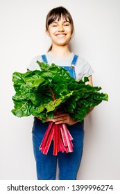 Happy girl in denim overalls holding a bunch of fresh swiss chard. Focus on the leaves