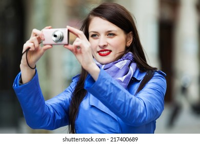 Happy girl with digital camera photographing travel destination