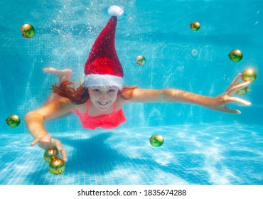 Happy girl dive and swim underwater with Christmas decoration balls wearing Santa Claus hat in the pool
