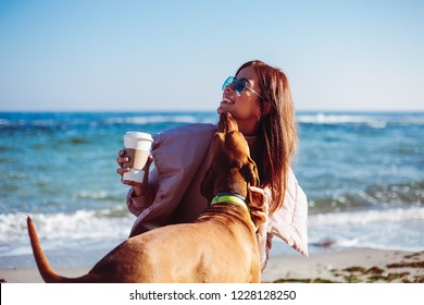 Happy Girl with a dog at the sea, stylish glamour girl in sunglasses, girl playing with a dog, pretty hipster girl, woman in stylish pink jacket, make up artist, coffee, sea life, outdoor, hair style
