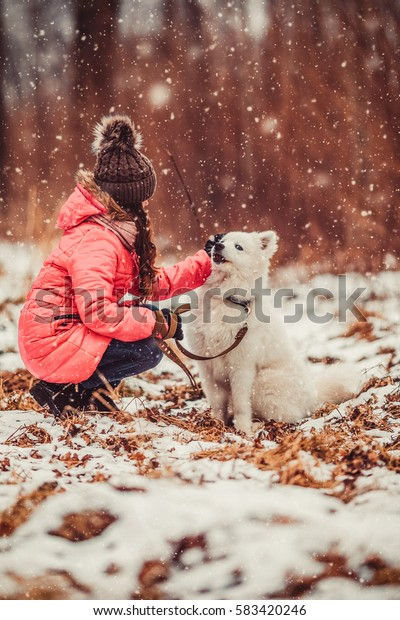 Happy girl with dog in winter forest