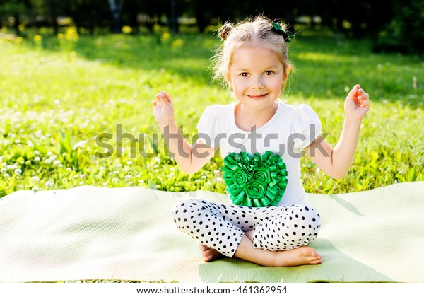 Happy girl doing yoga exercise outdoors